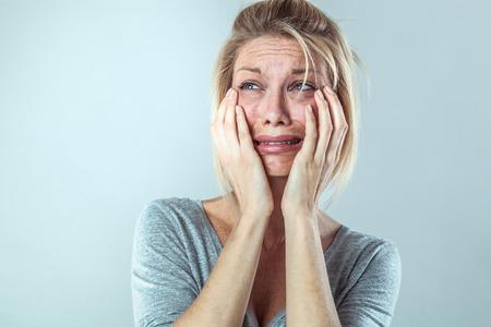drame concept - découragé jeune femme blonde dans la douleur avec de grosses larmes exprimant sa déception et de tristesse, gris studio de fond, contraste effets