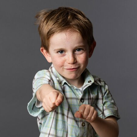 joyous: kid energy - joyous 5-year old red hair boy with freckles and summer checked shirt playing like a super hero with his fists in the foreground for fun childhood, grey background studio