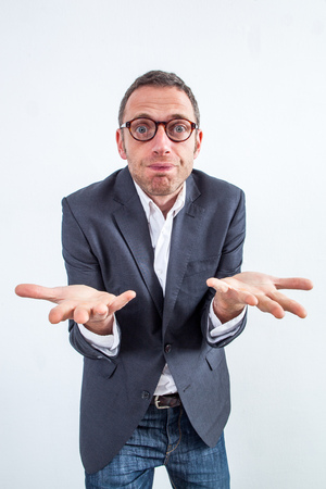 corporate denial concept - confused fun 40s businessman with hands in the foreground questioning management or denying his working attitude, wide angle view over white background Stock Photo
