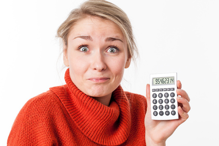 eyes wide: successful savings - funny young blond woman smiling with eyes wide open, enjoying showing her calculator with exciting financial solutions, isolated over white background