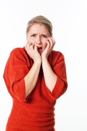 outraged: portrait of fear - outraged young blond woman hiding her face, biting her fingers against violence and danger, isolated white background Stock Photo