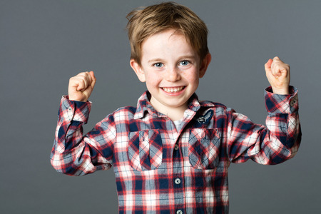 kid energy - smiling 5-year old red hair boy with freckles and checked shirt raising his strong fists for tough vitality, success and fun health, grey background studio