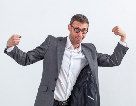 modern fighter: corporate fighter - funny modern office businessman showing his manager muscles for fun competition and impressive body language, wide angle view
