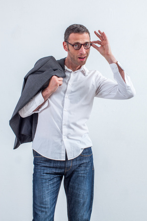 business for the middle: happy middle aged corporate man standing in holding his eyeglasses and jacket for fun perspective and business vision, white background studio