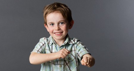 checked shirt: kid energy - dynamic young red hair child with freckles and summer checked shirt playing with his fists for fun game, grey background studio Stock Photo