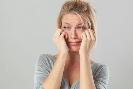 decepci�n: concepto de teatro - molesto joven mujer rubia llorando con grandes l�grimas expresando su decepci�n y tristeza, fondo gris estudio