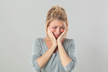 drama concept - heart broken young blond woman crying with big tears expressing her feelings under shock, grey background studio