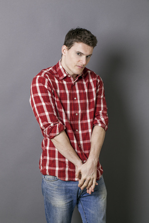 embarrassment: unhappy introvert young man looking down, holding his hands together for shyness, embarrassment or humiliation, grey background studio