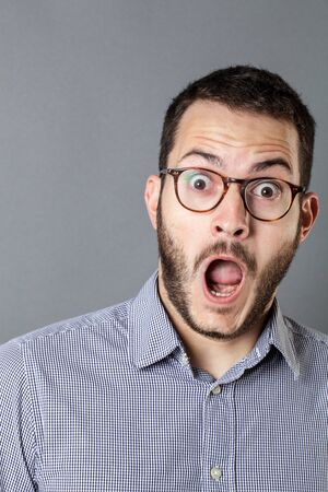 stunned: surprise concept - stunned young bearded businessman with eyeglasses and mouth open expressing amazement, grey background studio