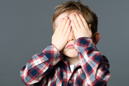 peekaboo: sad peekaboo - unhappy young child covering his eyes with his hands for sadness or not willing to see, grey background studio