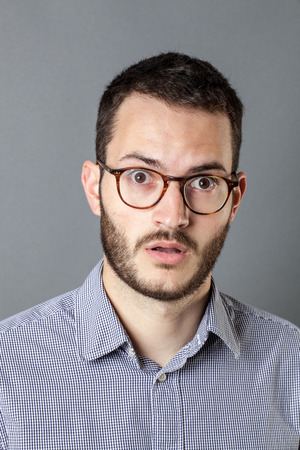 emptiness: surprise concept - speechless young bearded businessman with eyeglasses expressing emptiness, grey background studio