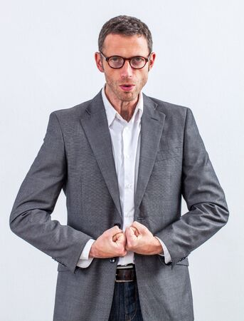 exasperation: corporate fighter - bossy middle aged manager with eyeglasses ready to loose his temper, impressing with big shoulders and strong fists together, grey background studio