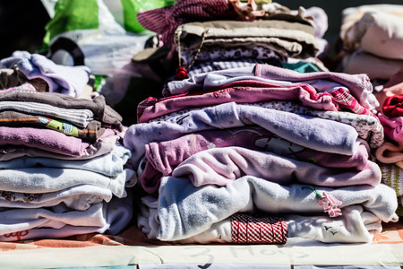reusing: display of second hand baby clothes and pyjamas for reusing, reselling,recycling,donating or welfare for second life sold at thrift store Stock Photo