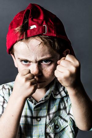 そばかすと赤い帽子と怖い若い子供バックの戦いとボクシング、演技学校で少しいじめのような灰色の背景スタジオでコントラスト効果