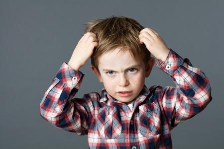piojos: muchacho joven molesto con pecas rasc�ndose el pelo para piojos o alergias, fondo gris estudio Foto de archivo