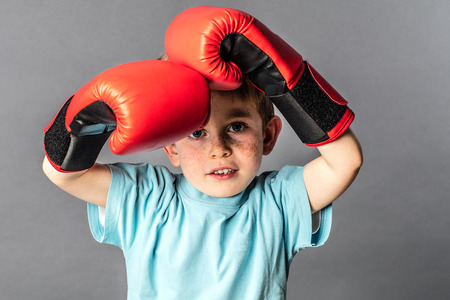 thinking young 5-year old boy with big boxing gloves protecting his face to fight or defend himself, grey background studio Stock Photo