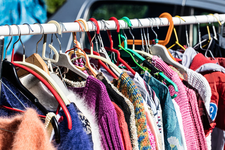 reusing: used colored female sweaters on rack for reselling,recycling,donating,reusing or thrift store for second life sold at flea market, springtime Stock Photo