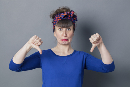 making a face: surprised young woman with thumbs down making a face, pouting with eyes wide open for amazement and disappointment, grey background studio Stock Photo