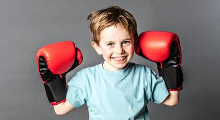 happy young 6-year old boy with red hair and freckles smiling and holding his big boxing gloves up to win a sporty competition, grey background studio Фото со стока - 57746158