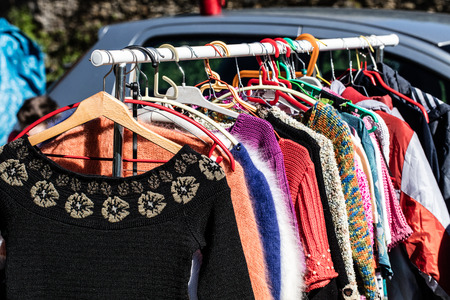 thrift: display of fast fashion women dresses and jackets on rack for reselling,donation,reusing or thrift store for second life sold at flea market, outdoors