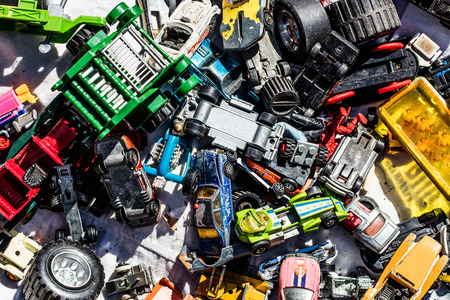 thrift store: full flat lay of boy car toys made of cheap plastic or vintage models in bulk display at garage sale or flea market for over-consumption society, outdoors