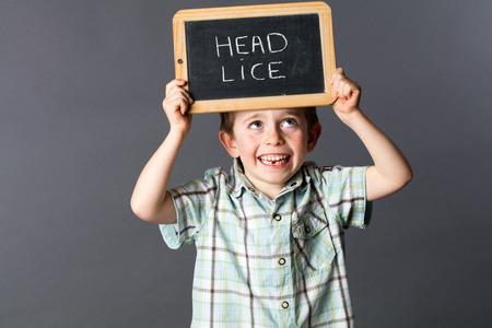 piojos: muchacho joven sonriente de pie y sosteniendo una pizarra en la escuela divertido como una advertencia de piojos de la cabeza para protestar y luchar contra el enemigo pelo, fondo gris estudio