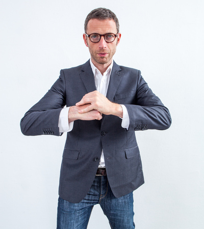 calming: corporate fighter - tensed middle aged modern businessman with eyeglasses waiting with fists together and calming hand gesture, light grey background studio Stock Photo