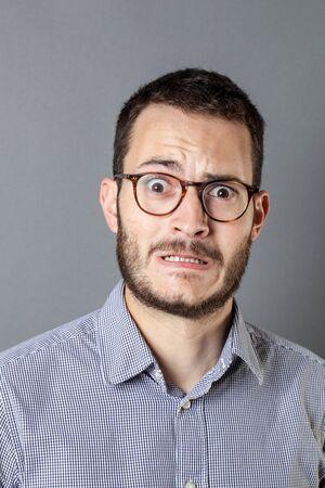 portrait de la peur - peur jeune entrepreneur barbu avec des lunettes de meulage des dents pour le stress d'affaires et de l'anxiété, gris studio de fond