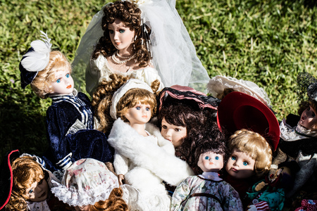 reusing: display of various vintage and old ceramic dolls for collectors and collection at garage sale of flea market, outdoors