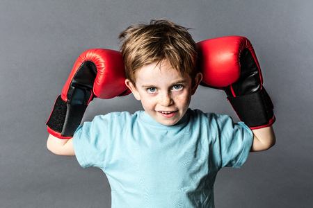 mischievous: mischievous young boy with red hair and freckles holding his boxing gloves up to win a sporty competition, grey background studio Stock Photo