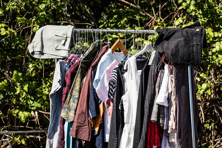 reusing: display of old fashion women clothing on rack for charity,donation,reusing or reselling for second life sold at flea market, outdoors