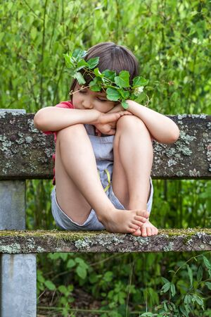 eyes closing: tired young kid closing her eyes to sleep, leaning her face on her hands, sitting with bare feet in summertime over natural green bushes and mossy bench Stock Photo