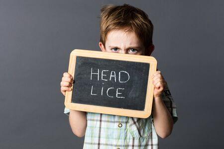 piojos: disgustado niño en edad preescolar ocultarse detrás de una pizarra de la escuela con 'poux' escrito en francés para asustar y luchar contra los piojos de la escuela, estudio de fondo gris