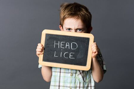 lice: displeased preschool child hiding himself behind a school slate with poux written in French to scare and fight against school head lice, grey background studio