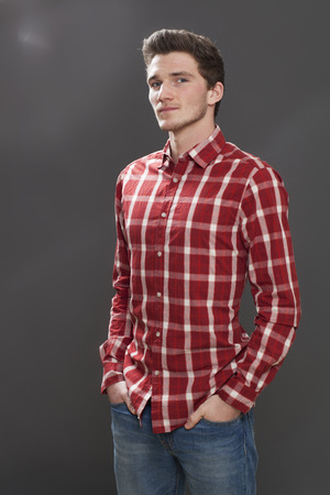 arrogant teen: proud young man with hands in jeans pocket standing for a cool student portrait, grey background studio Stock Photo