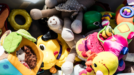 reusing: recycling baby toys and teddies made of cheap plastic or fabric in bulk display at garage sale of flea market for over-consumption society, outdoors