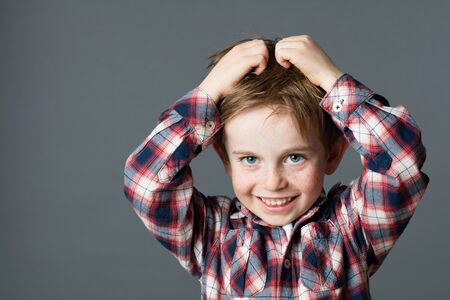 lice: smiling young boy with freckles scratching his hair for head lice or allergies, grey background studio Stock Photo
