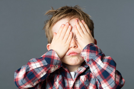 peekaboo: fun peekaboo - pouting young kid covering his eyes with his hands to be invisible or not willing to see, grey background studio Stock Photo
