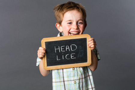 lice: excited little child with red hair warning about head lice to fight against at school with writing slate as fun health shield, grey background studio