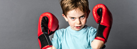 conflicted: fighting beautiful young kid with freckles and red hair showing his boxing gloves up, looking aggressive for competition, grey background studio Stock Photo