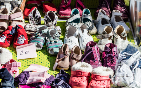 reusing: display of used girl baby and child shoes for charity,donating,reusing or reselling for second life sold at garage sale at springtime