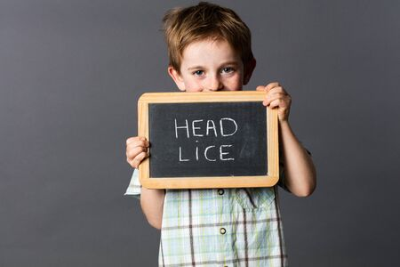 informing: ashamed preschool boy with red hair informing about head lice to fun fight against at school, grey background studio Stock Photo