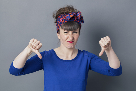 pouting: sick young woman with thumbs down making a face, pouting and frowning for disgust and disappointment, grey background studio Stock Photo