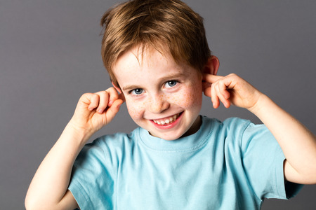 cute attitude: smiling cheeky young boy with blue eyes and freckles teasing, covering his closed ears, ignoring his parent scolding with attitude, grey background