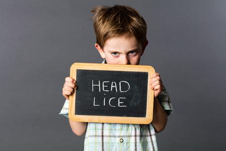 piojos: verg�enza escondite ni�o de 6 a�os o protegerse a s� mismo detr�s de una pizarra de la escuela como un escudo piojos de la cabeza para asustar y luchar contra el enemigo, fondo gris estudio