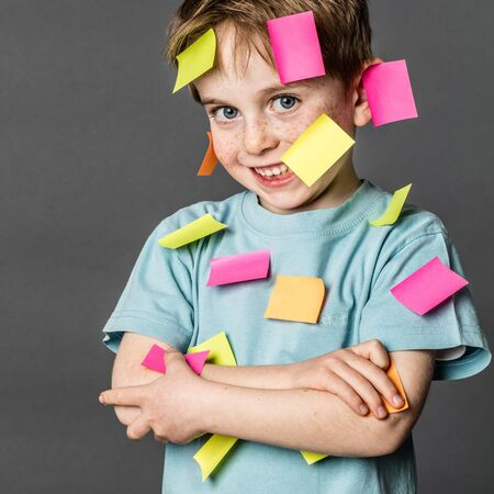 multi-tasking preschool activity - cute 6-year old boy with freckles smiling with copy space sticky notes all over the body to remember all his ideas, indoors