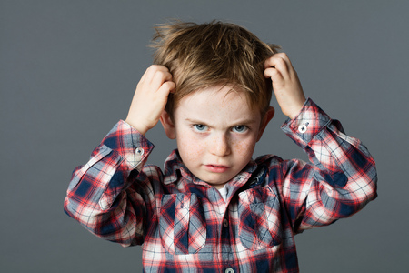 itchy: mischievous unhappy 6-year old kid with freckles scratching his hair for head lice or allergies, grey background studio Stock Photo