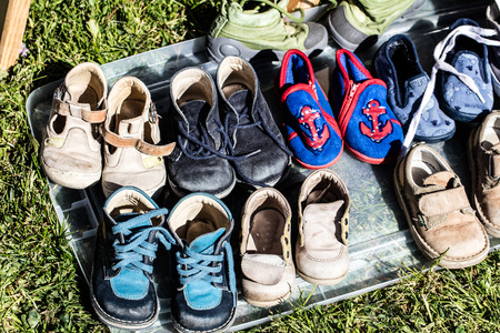 reusing: display of second hand baby and child shoes for charity,donation,reusing or recycling for second life sold at garage sale at springtime
