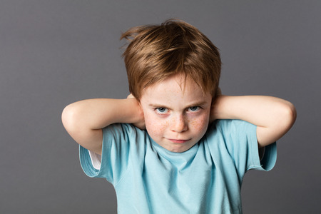 stubborn: stubborn young kid with freckles teasing, covering his closed ears, ignoring his parent scolding with attitude, asking for silence, grey background