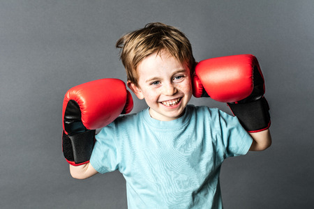 giggling: thrilled young 6-year old boy with red hair giggling and holding his big boxing gloves up for a fight, grey background studio Stock Photo